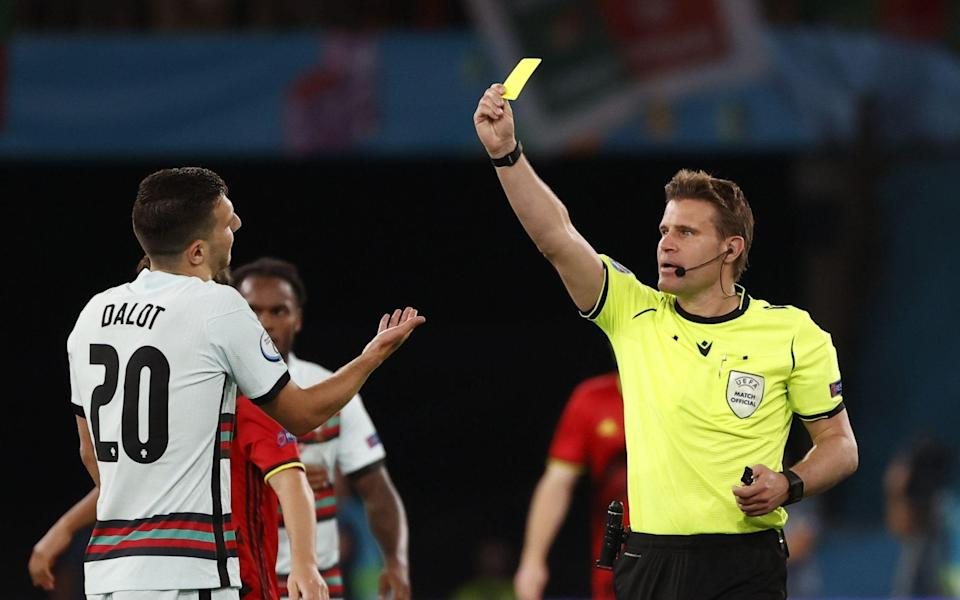 German referee Felix Brych shows the yellow card to Diogo Dalot - Shutterstock