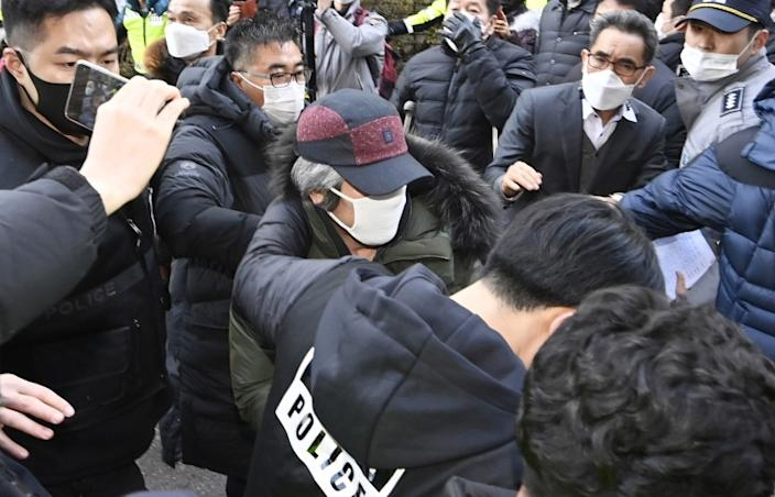 Cho Doo-soon, center, escorted by police officers, arrives home in Ansan, South Korea