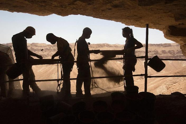 Israeli and foreign volunteers take part in an excavation in search for archaeological artifacts at a cave in the Tzeelim Canyon above the Dead Sea, in the Judean desert in Israel, on June 1, 2016 (AFP Photo/Menahem Kahana)