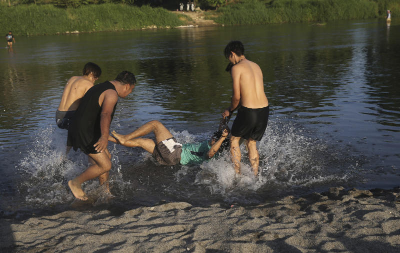 Honduran migrants joke around as they bathe in the Suchiate River, which creates a natural border between Guatemala, below, and Mexico, top, near Tecun Uman, Guatemala, Wednesday, Jan. 22, 2020. The number of migrants stuck at the Guatemala-Mexico border continued to dwindle Wednesday as detentions and resignation ate away at what remained of the latest caravan. (AP Photo/Marco Ugarte)