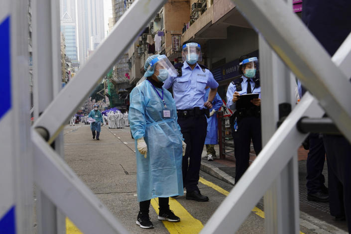 Police officers and health officials stand guard at the Yau Ma Tei area, in Hong Kong, Saturday, Jan. 23, 2021. Thousands of Hong Kong residents were locked down Saturday in an unprecedented move to contain a worsening outbreak in the city, authorities said. (AP Photo/Vincent Yu)