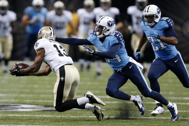 Tennessee Titans cornerback Coty Sensabaugh (24) and free safety George Wilson (21) pursue as New Orleans Saints wide receiver Joe Morgan (13) pulls in a long pass reception in the second half of a NFL preseason football game in New Orleans, Friday, Aug. 15, 2014. (AP Photo/Rogelio Solis)