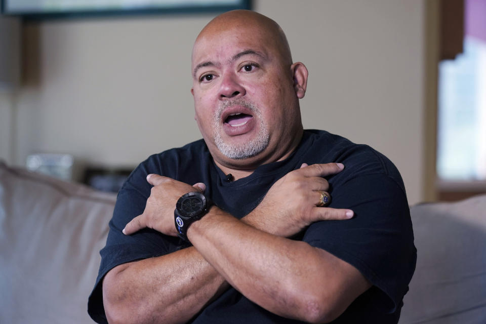 """Will Jimeno, the former Port Authority police officer who was rescued from the rubble of the attacks at the World Trader Center, shows how he crossed his arms with the signs for """"I Love You,"""" during an interview in his home in Chester, N.J., Monday, Aug. 2, 2021. It was to be a sign to his family if he died in the rubble. (AP Photo/Richard Drew)"""