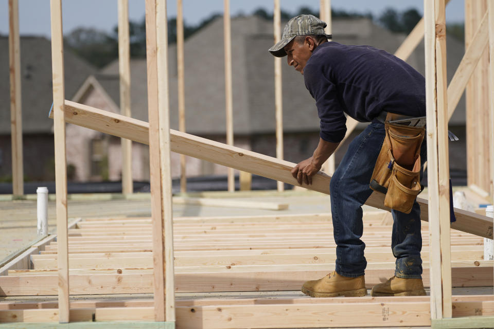 FILE - In this March 16, 2021 file photo, a carpenter aligns a beam for a wall frame at a new house site in Madison County, Miss. U.S. construction spending rose a modest 0.2% gain in April as strength in housing offset further weakness in nonresidential construction. (AP Photo/Rogelio V. Solis, File)