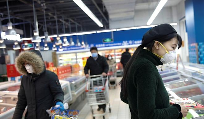 People wearing face masks look for products at a supermarket, as the country is hit by an outbreak of the new coronavirus, in Beijing, China February 19, 2020. REUTERS/Carlos Garcia Rawlins
