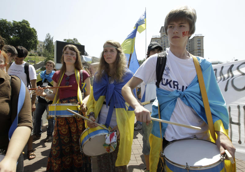 Opposition protesters beat the drums during the march in central Kiev, Ukraine, Thursday, July 5, 2012. About 1,000 opposition activists were rallying in the capital of Ukraine on Thursday to protest legislation upgrading the status of the Russian language. The Ukrainian parliament passed the bill Tuesday that would allow the use of Russian in courts, education and other government institutions in Russian-speaking regions of the country. The inscription on the face, 'Veto'. (AP Photo/Efrem Lukatsky)