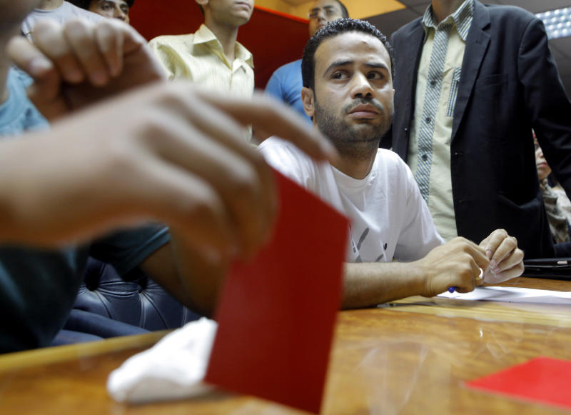 Mahmoud Badr, a leader of the Tamarod, or rebel, movement calling for the ouster of Egypt's president talks as a member holds a red card during a press conference in Cairo, Saturday, June 29, 2013. The youth group leading the campaign against Egypt's president says it has collected the signatures of 22 million Egyptians who want to remove the Islamist leader. Badr said Saturday that 22,134,460 Egyptians have signed the petition demanding President Mohammed Morsi's ouster.(AP Photo/ Amr Nabil)