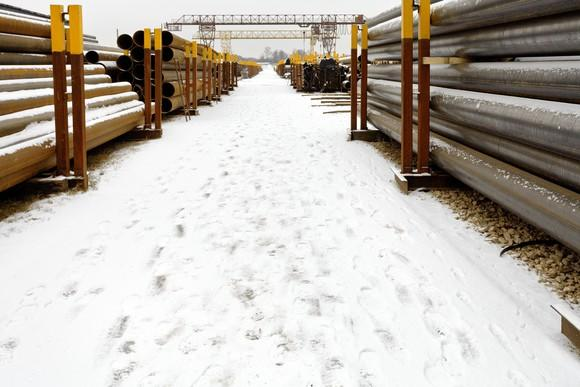 Neat stacks of pipes facing one another with snow on the ground in between