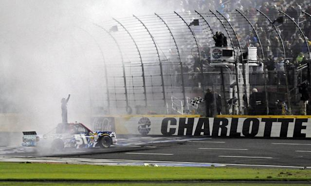 Kyle Busch celebrates after winning the NASCAR Trucks series auto race at Charlotte Motor Speedway in Concord, N.C., Friday, May 16, 2014. (AP Photo/Mike McCarn)