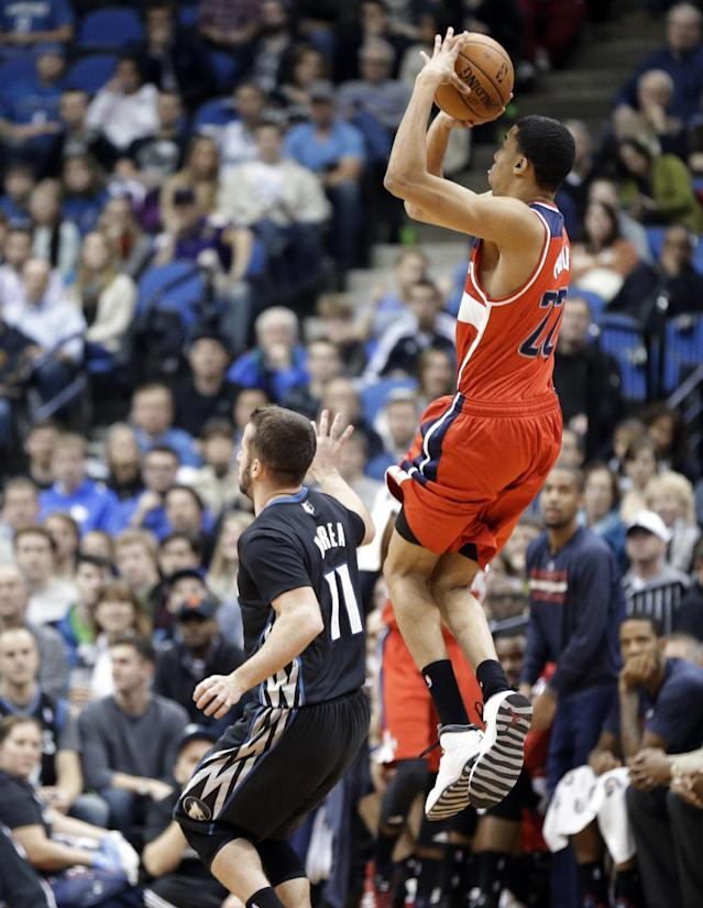 Washington Wizards' Otto Porter Jr., right, shoots a jumper as Minnesota Timberwolves' J.J. Barea watches during the first quarter of an NBA basketball game, Friday, Dec. 27, 2013, in Minneapolis. (AP Photo/Jim Mone)