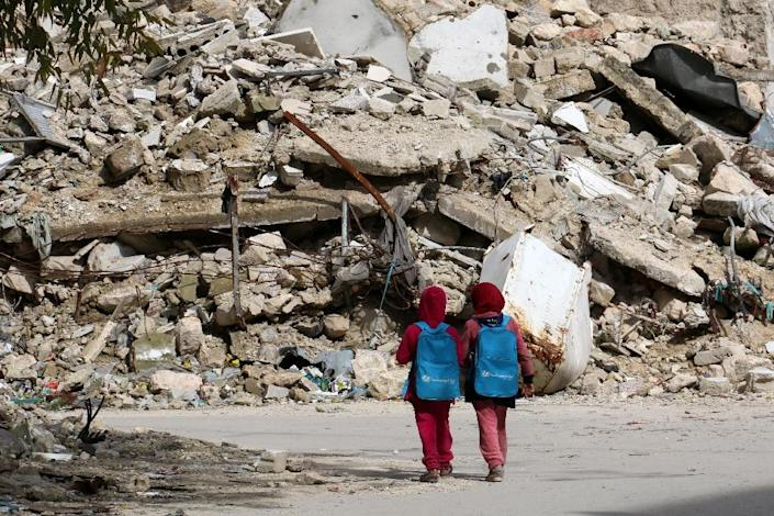 Syrian girls, carrying school bags provided by UNICEF, walk past the rubble of destroyed buildings on their way home from school on March 7, 2015 in the rebel-held side of the northern Syrian city of Aleppo (AFP Photo/Zein al-Rifai)