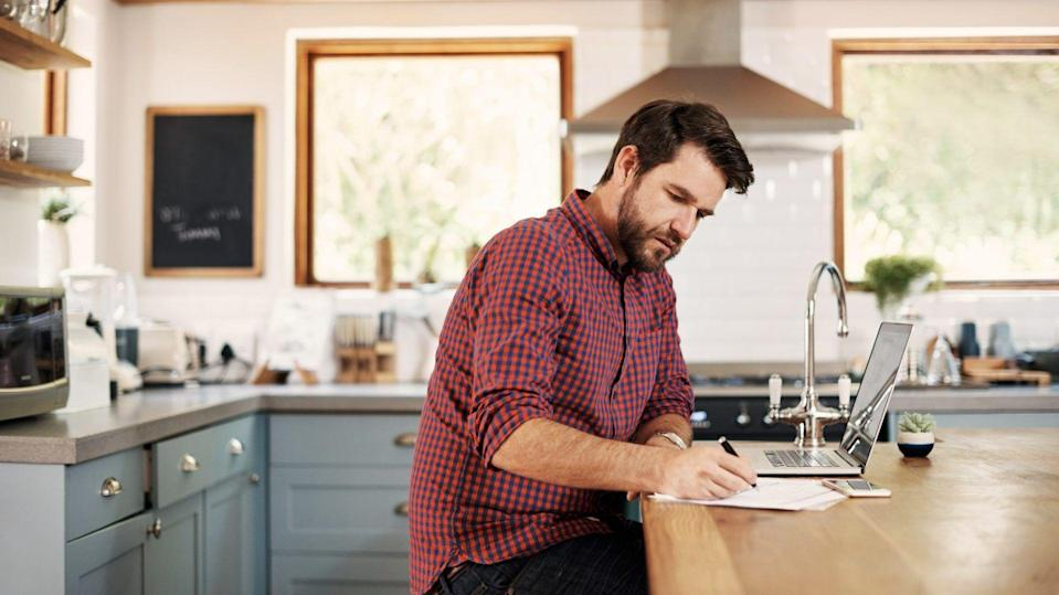 Shot of a handsome man sitting at his kitchen counter with his laptop.