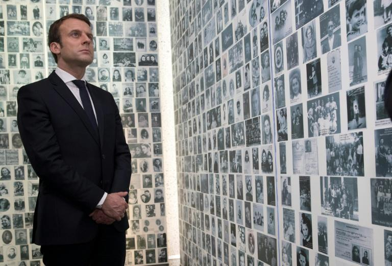 Presidential candidate Emmanuel Macron looks at some of the 2,500 photographs of young Jews deported from France during WWII, as he visits the Shoah Memorial in Paris