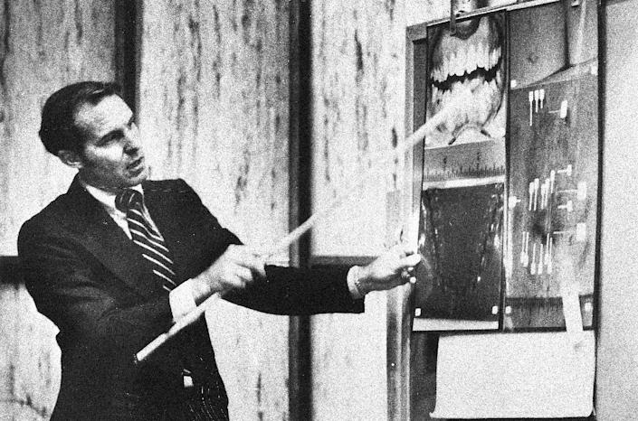 This July 18, 1979, photo, shows forensic odontologist Dr. Richard Souviron pointing to a blown-up photograph of accused murderer Theodore Bundy's teeth during Bundy's murder trial in Miami, Fla. Souviron, one of the prosecution's key witnesses, showed the jury that only Bundy's teeth could have made the bite marks discovered on the buttocks of one of the slain co-eds in the Chi Omega murder case. (AP Photo)