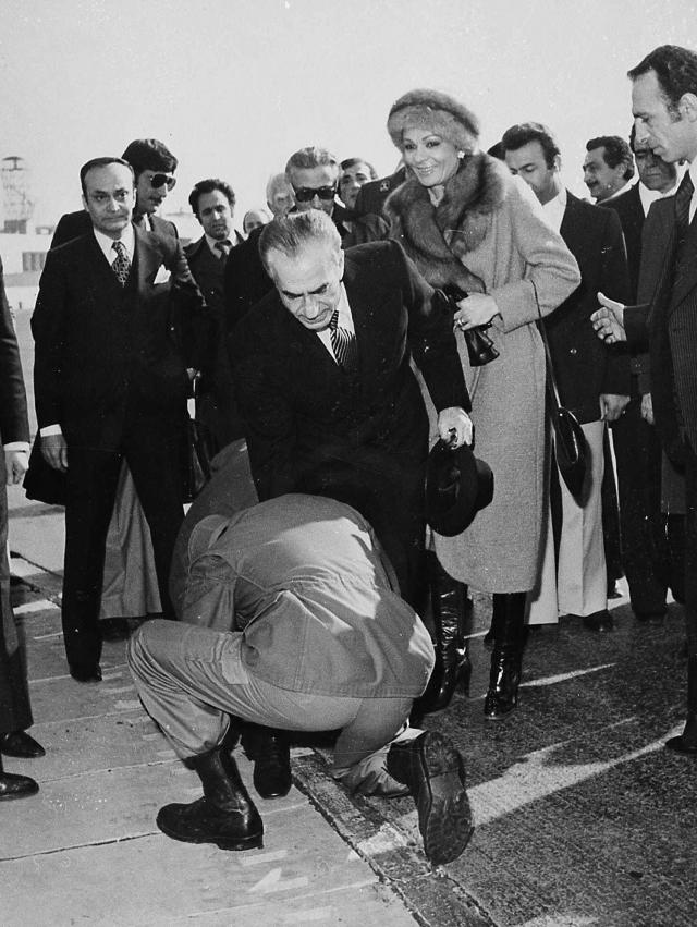 FILE - In this Jan. 16, 1979 file photo, a soldier bends to kiss the feet of Iran's Shah Mohammad Reza Pahlavi on the tarmac of Mehrabad Airport in Tehran, Iran. Behind the shah is his wife, Empress Farah. Wednesday, Jan. 16, 2019 marks the 40th anniversary of the shah abandoning his Peacock Throne and leaving his nation for the last time in his life, setting the stage for the country's 1979 Islamic Revolution only a month later. (AP Photo, File)