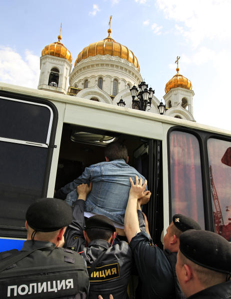 """Police officers detain an opposition activist near the Moscow's Christ the Savior Cathedral in Moscow, Sunday, April 29, 2012. Opposition activists planned to pray to Holy Mother to deliver Russia from Vladimir Putin. They planned to repeat the """"punk prayer"""" by five members of the feminist band Pussy Riot briefly who seized the pulpit of Moscow's Christ the Savior Cathedral in February and chanted """"Mother Mary, drive Putin away."""" Three band members have been arrested and now face up to seven years in jail on charges of hooliganism. (AP Photo/Sergey Ponomarev)"""