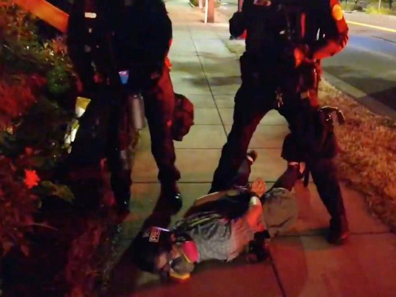 Journalist Justin Yau lies handcuffed on the ground with police officers standing over him at a demonstration in Portland, Oregon: ALEX MILAN TRACY via REUTERS