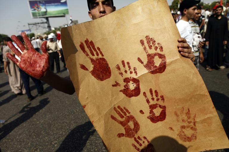 A supporter of the Muslim Brotherhood and ousted Egyptian president Mohamed Morsi shows his blood-stained hand while holding a placard bearing handprints made with the blood of victims who were shot during a gun battle