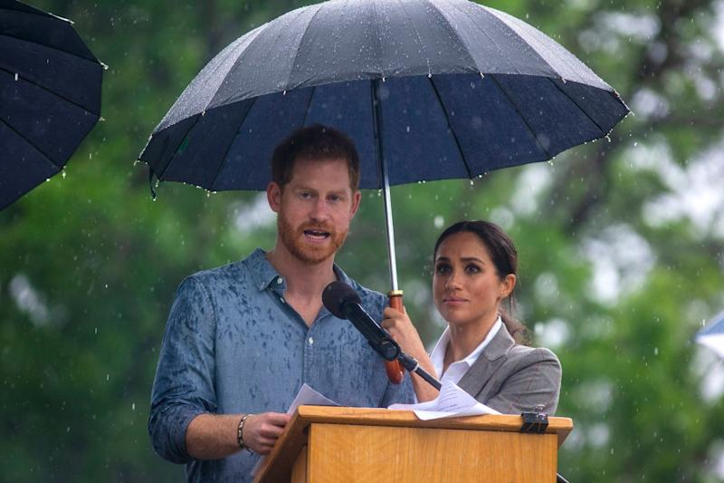 Double act: The Duchess of Sussex holds an umbrella as Prince Harry makes a speech at a community picnic in Victoria Park in Dubbo (PA)