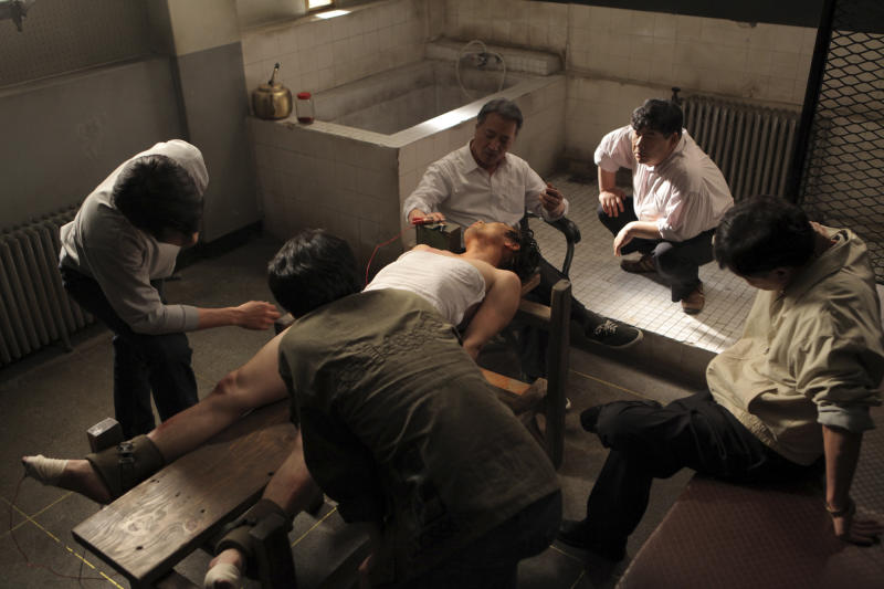 """In this undated photo released on Friday, Oct. 5, 2012 by Busan International Film Festival, South Korean actor Lee Kyeong-yeong, third from right on a chair, acts as a torturer in a scene from the film """"National Security."""" The film based on the memoir of a democracy activist who was tortured in the 1980s by South Korea's military rulers is provoking discussion about the country's not-so-distant authoritative past and the influence it will have on this year's presidential election. (AP Photo/Busan International Film Festival) EDITORIAL USE ONLY"""