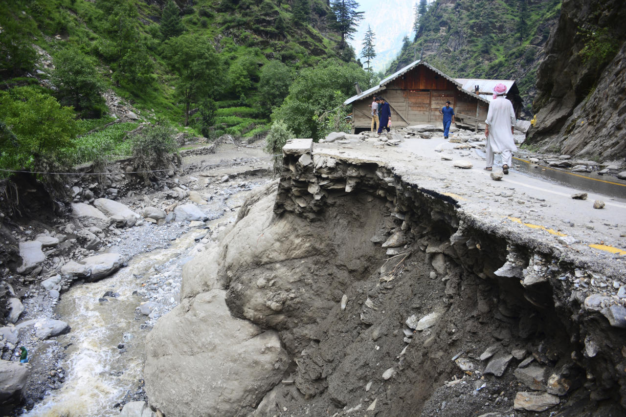 Villagers walk along a road washed away by heavy flooding in Neelum Valley of Kashmir, Monday, July 15, 2019. Pakistan says many people are missing and feared dead after heavy rains triggered flash floods in Kashmir. Ahmed Raza Qadri, the Pakistani minister for disaster management in the disputed territory, says the flooding late on Sunday also caused much destruction and damage in the village of Lesswa in Neelum Valley. (AP Photo/M.D. Mughal)