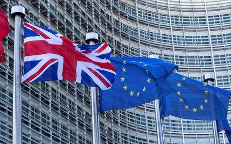 FILE PHOTO: Union Jack flag flutters next to EU flags ahead of a visit from Britain's PM Cameron at the EU Commission headquarters in Brussels
