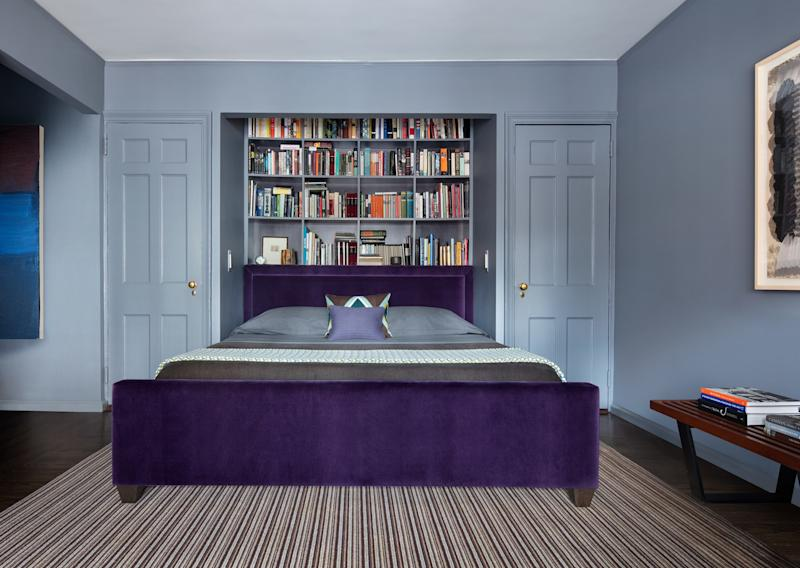 Rabel installed additional book storage in the bedroom, behind a custom-made bed that's upholstered in an aubergine velvet by Schumacher and topped with bedding by Deborah Sharpe Linens. The rug is from Kravet, and the vintage bench is by George Nelson.