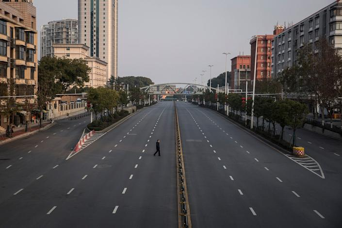 A man crosses an empty highway road on February 3, 2020 in Wuhan.