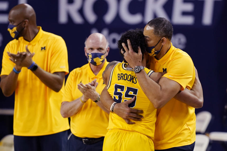 Michigan guard Eli Brooks (55) is hugged by coach Juwan Howard after being removed during the second half of the team's NCAA college basketball game against Michigan State, Thursday, March 4, 2021, in Ann Arbor, Mich. (AP Photo/Carlos Osorio)