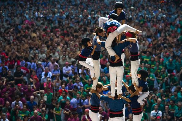 TARRAGONA, SPAIN - OCTOBER 07: Members of the Colla 'Caprogossos de Mataro' climb up as they construct a human tower during the 24th Tarragona Castells Comptetion on October 7, 2012 in Tarragona, Spain. The 'Castellers' who build the human towers with precise techniques compete in groups, known as 'colles', at local festivals with aim to build the highest and most complex human tower. The Catalan tradition is believed to have originated from human towers built at the end of the 18th century by dance groups and is part of the Catalan culture.  (Photo by David Ramos/Getty Images)