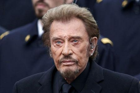 FILE PHOTO: French singer Johnny Hallyday attends a ceremony at Place de la Republique square to pay tribute to the victims of last year's shooting at the French satirical newspaper Charlie Hebdo, in Paris, France, January 10, 2016.  REUTERS/Charles Platiau/File Photo