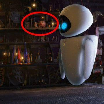 """<p>There's room for lots of hidden references among Wall-E's junk, but our favorite is a brief cameo by <em>Toy Story</em>'s Hamm — it's on the shelf behind Eve. The voice of Hamm is provided by <a href=""""https://www.imdb.com/name/nm0001652/"""" rel=""""nofollow noopener"""" target=""""_blank"""" data-ylk=""""slk:John Ratzenberger"""" class=""""link rapid-noclick-resp"""">John Ratzenberger</a>, who is often considered an Easter egg in his own right, because Pixar has found a way to <a href=""""https://ratzenberger.com/pixar-characters/"""" rel=""""nofollow noopener"""" target=""""_blank"""" data-ylk=""""slk:slip his voice into every single one of their movies"""" class=""""link rapid-noclick-resp"""">slip his voice into every single one of their movies</a>. (He only says one word in <em>Coco</em>: """"Gracias."""")</p>"""
