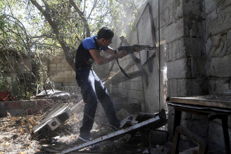 A Free Syrian Army fighter takes a shooting position in Sheikh Khodr area in Aleppo