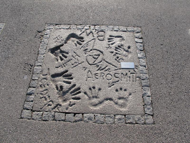 Band hands and names in cement.