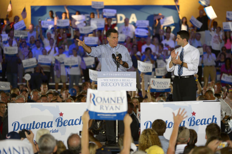 Republican presidential candidate, former Massachusetts Gov. Mitt Romney, left, addresses supporters as his vice presidential running mate Rep. Paul Ryan, R-Wis., listens at the Daytona Beach Historic Bandshell during the Romney Ryan Victory Rally in Daytona Beach, Fla., Friday, Oct. 19, 2012. (AP Photo/Phelan M. Ebenhack)