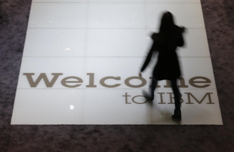 A woman walks over a welcoming sign at the booth of IBM at the CeBIT trade fair in Hanover