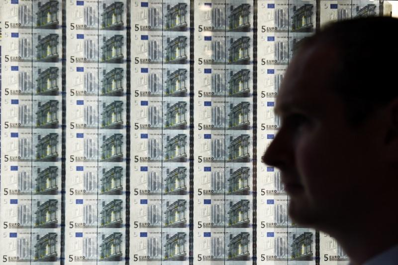 A man is seen in front of a sheet of five Euro notes at the opening of the new Central Bank of Ireland offices in Dublin