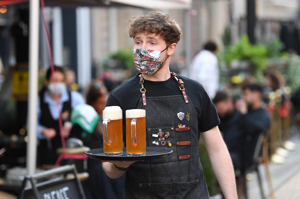 CARDIFF, WALES - APRIL 26: A waiter carries a tray of pints on April 26, 2021 in Cardiff, Wales. Outdoor hospitality reopens today in Wales and it is expected indoor hospitality will reopen from May 17. The infection rate across Wales now stands at 12.9 cases per 100,000 people for the seven days up to April 21. (Photo by Matthew Horwood/Getty Images)