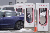 A Tesla electric vehicle, left, sits in a charging station at a dealership, Thursday, Feb. 18, 2021, in Dedham, Mass. After a year of ghostly airports, empty sports stadiums and constant Zoom meetings, growing evidence suggests that the economy is strengthening. Hiring picked up in February 2021. Business restrictions have eased as the pace of viral infections has ebbed. Yet the economy remains far from normal. (AP Photo/Steven Senne)