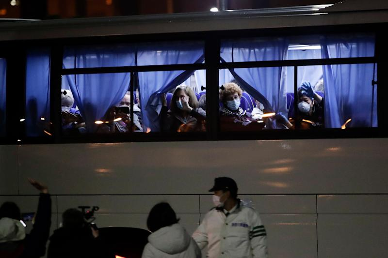 Buses carrying American passengers from the quarantined Diamond Princess cruise ship leave a port in Yokohama, near Tokyo, on Monday. (ASSOCIATED PRESS)