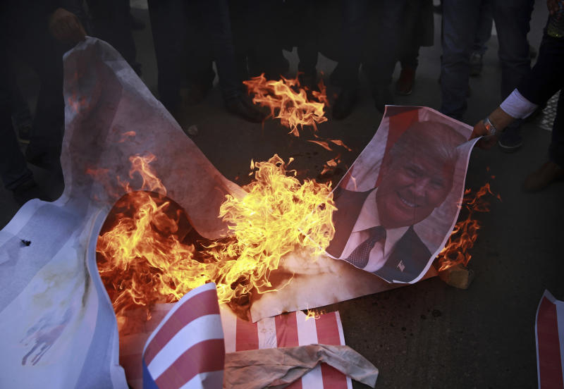Palestinians burn a poster of U.S. President Donald Trump and a representation of an American flag, during a protest against the U.S. decision to recognize Jerusalem as Israel's capital, in Gaza City Thursday, Dec. 7, 2017. (AP Photo/ Khalil Hamra)
