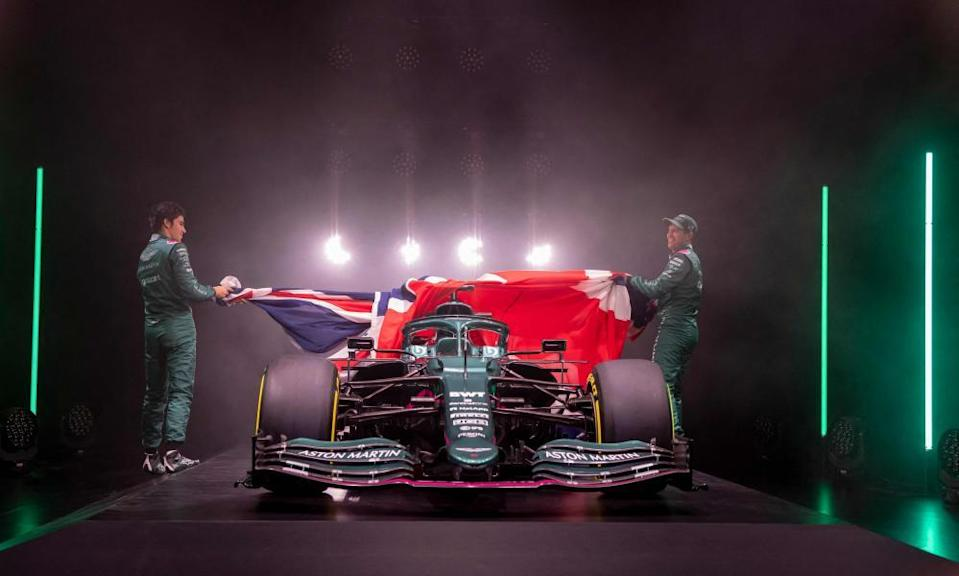 Lance Stroll and Sebastian Vettel pull back a union jack to unveil Aston Martin's car for the 2021 season.