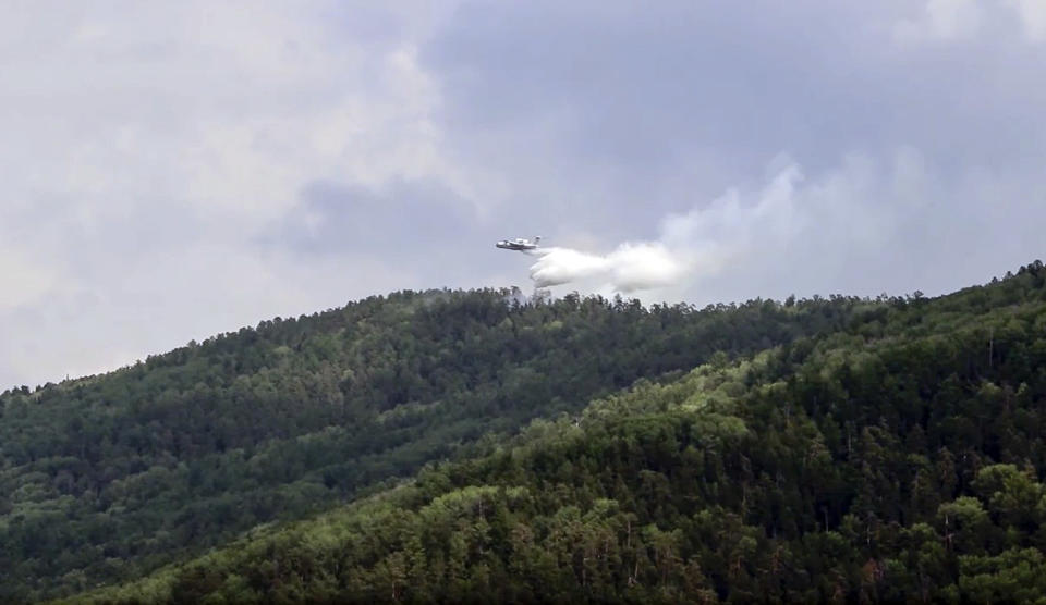 This image taken from video provided by Russian Emergency Ministry, shows a Russian Emergency Ministry's Beriev plane BE-200 Be-200 multipurpose amphibious aircraft releases water extinguishing in the Trans-Baikal National Park in Buryatia, southern Siberia, Russia, Friday, July 10, 2020. A summer heatwave across Siberia has spread the area of forestfires, with Irkutsk region northbound on Lake Baikal experiencing at least 50 fires, Russian state television reported Friday. According to Greenpeace, three million hectares of forest are currently under fire in Siberia. (Russian Emergency Ministry Press Service via AP)