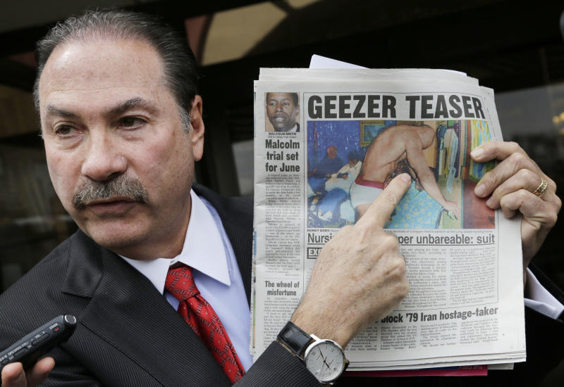 Attorney Howard Fensterman, representing the East Neck Nursing and Rehabilitation Center, points to a newspaper article about the nursing home during a news conference, Tuesday, April 8, 2014. in West Babylon, N.Y. The nursing home hired a male exotic dancer to perform for its patients, according to a lawsuit filed by facility resident Bernice Youngblood in State Supreme Court in Suffolk County. Fensterman acknowledged the home hired the dancer, but said that Youngblood's attendance was voluntary. (AP Photo/Mark Lennihan)