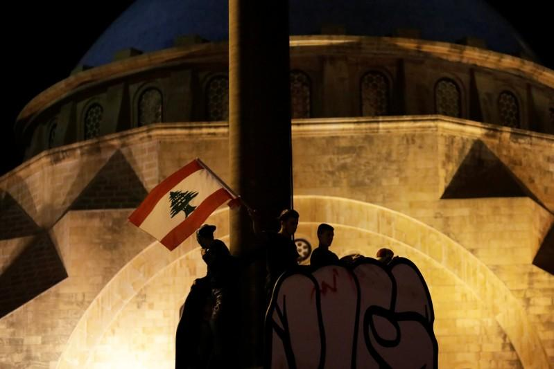 Protesters stand on the top of a structure at a demonstration during ongoing anti-government protests in Beirut