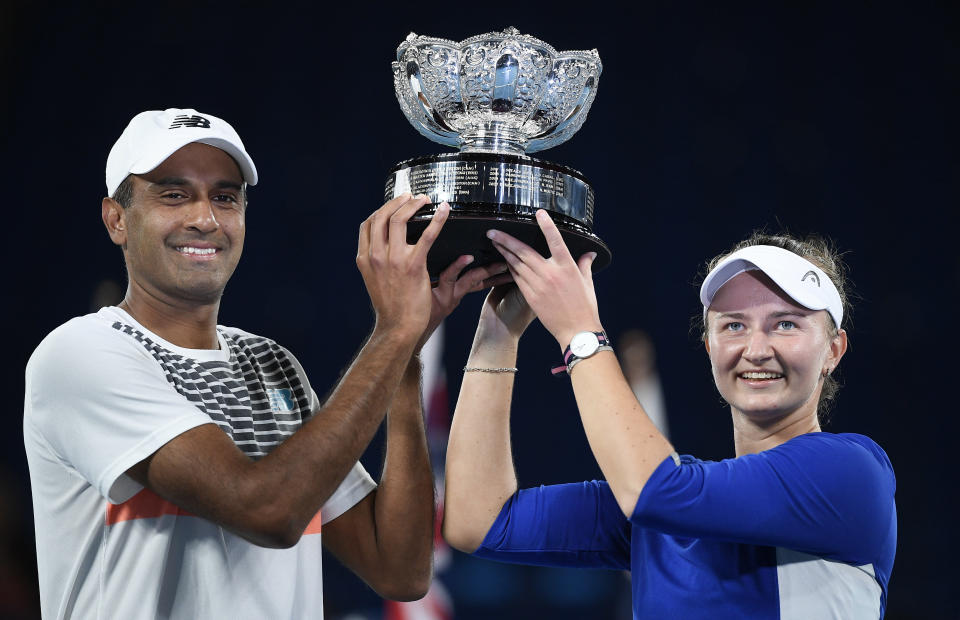 Rajeev Ram of the US and Barbora Krejcikova of the Czech Republic hold their trophy after defeating Australia's Samantha Stosur and Matthew Ebden in the mixed doubles final at the Australian Open tennis championship in Melbourne, Australia, Saturday, Feb. 20, 2021.(AP Photo/Andy Brownbill)