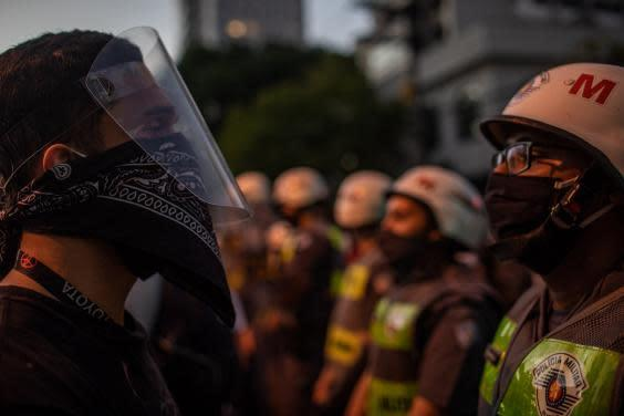 Pro-democracy protesters face off with military police during a protest against Bolsonaro (Getty Images)