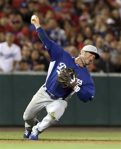 Los Angeles Dodgers shortstop Nick Punto throws to first base for an out on Los Angeles Angels' Albert Pujols in the sixth inning of an exhibition baseball game in Anaheim, Calif., on Saturday, March 30, 2013. (AP Photo/Christine Cotter)