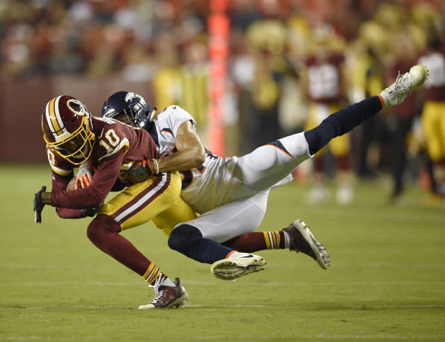 Washington Redskins wide receiver Paul Richardson (10) is tackled by Denver Broncos defensive back Justin Simmons during the first half of a preseason NFL football game, Friday, Aug. 24, 2018, in Landover, Md. (AP Photo/Nick Wass)