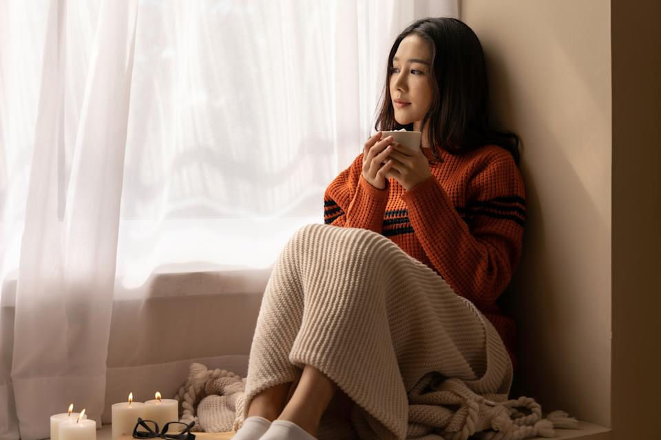 An Asian woman wearing a sweater inhaled the scent and drank the winter morning coffee. She looked at the view from the large window on vacation.